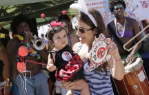 A woman and child in costume dance during a street carnival at which health workers distributed kits with information about the Zika virus, on Ipanema beach in Rio de Janeiro, Brazil.