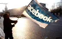 A protester in Russia waves a Facebook flag.