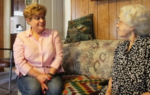 Lucy Oliveira of the New Bedford Immigrants' Assistance Center sits with 86-year-old Margarida Xavier, who moved to the US from Portugal in the 1960s. Oliveira visits Xavier's home every month and often helps Xavier read her mail.