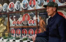 A man poses for pictures in front of souvenir plates featuring portraits of former and current Chinese leaders including President Xi Jinping and the late Chairman Mao Zedong in Tiananmen Square in Beijing, Feb. 26, 2018.