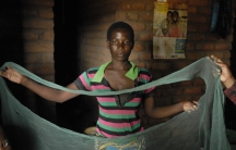 Dorothy Kalema holds up her bed net with large holes.