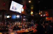 People sitting at a bar with a screen showing Donald Trump and Hillary Clinton above