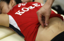 South Korea's women's national volleyball player Lee Sook-ja undergoes an acupuncture session with Park Ji-hun, the oriental doctor in charge of the team, at a gym in Jincheon, 150 km south of Seoul, July 5, 2012.