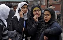 Kashmiri girls stand on a roadside
