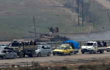 Forces loyal to Syria's President Bashar al-Assad sit on a tank as a convoy of buses and other vehicles try to evacuate
