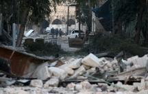 People walk near rubble of damaged buildings