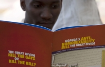 A man reads a publication by a civil society coalition on human rights and constitutional law in Kampala.