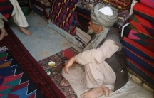"""A man selling handwoven rugs in the city of Quetta, in western Pakistan. While the """"war rugs"""" are in demand in Western countries, their value in the local Pakistani market is very low."""