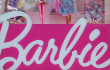 Barbie dolls are seen in a window of a toy store.