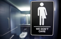 A sign protesting a recent North Carolina law restricting transgender bathroom access adorns the bathroom stalls at the 21C Museum Hotel in Durham, North Carolina