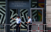 Security officers stand outside the U.S. Embassy in Berlin July 10, 2014. Germany asked the top U.S. intelligence official at the Berlin embassy on Thursday to leave the country, a highly unusual step reflecting the deep anger within Angela Merkel's gover