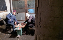 Two migrants play checkers with bottle caps in an abandoned warehouse where they live on the Greek island of Lesbos.