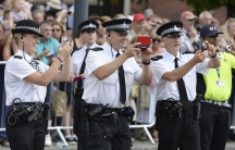 Police officers take pictures of giant puppets as they move through the streets of Liverpool, northern England July 25, 2014.