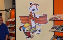 A painting of Calvin and Hobbes graces the wall of a comic book shop.