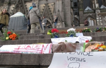 Flowers and handwritten signs for the sexual assault victims have been left on the steps of Cologne's Gothic cathedral. Hundreds of women reported being victimized in this area during a chaotic New Year's Eve.
