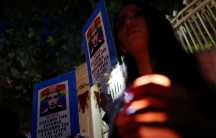 Members of the LGBT community hold a placard with the picture of Russia's President Vladimir Putin during a protest outside the Russian embassy in Mexico City.