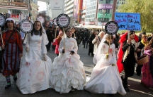 Women activists, some dressed in wedding gowns representing child brides forced into marriage, hold placards that read