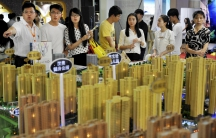 Sales representatives talk to potential buyers in front of a model of a residential complex at a real estate exhibition in Wuhan, Hubei province, China, on May 10, 2015.