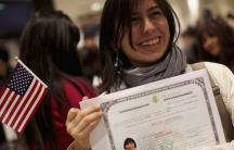 Anais Arias-Aragon poses for pictures with her certificate after receiving proof of U.S. citizenship
