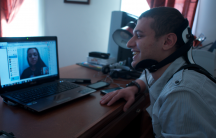 Fouad Faris, 19, sits at his computer in Shrewsbury, MA, video chatting with his sister, Rama, who is in Turkey. Faris wears a neck brace because he is recovering from a biking accident.