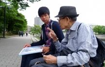 Masaaki Murakami, a volunteer guide at Hiroshima's Peace Memorial Park listens to 87-year-old atomic bomb survivor Noriho Azuma.