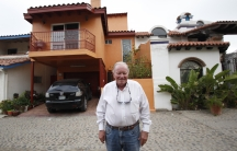 Gil Devine in front of his home in Mexico, near the border.  Devine commutes to work six days a week in San Diego.