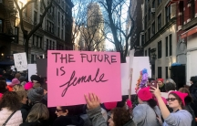 """A pink sign reading, """"The future is female"""" is hoisted above the crowds of marchers, some of whom are wearing the signature pink pussy hats."""