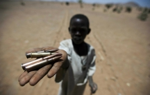 A child holds bullets picked from the ground, in Rounyn, a village located about 15 kilometers north of Shangil Tobaya, North Darfur, Sudan, on March 27, 2011.
