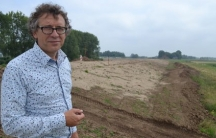"Dutch ecologist and dike designer Mindert de Vries stands on top of one of the new ""soft"" dikes being built near the Rhine River delta city of Dordrecht. Dutch innovations in flood control are helping reduce the adverse effects of older dike technologies."