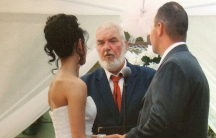 Couple looks at wedding officiant in ceremony