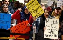 Dozens of pro-immigration demonstrators cheer and hold signs as international passengers arrive at Dulles International Airport