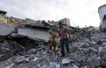 People walk past debris of a collapsed building