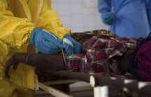 Medical staff take a blood sample from a suspected Ebola patient at the government hospital in Kenema, July 10, 2014.