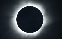 The sun is blacked out and surrounded by a ring of bright light during a total solar eclipse.