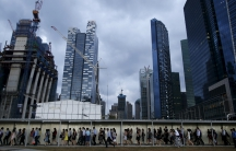 Commuters walk to the train station during evening rush hour in the financial district of Singapore March 9, 2015.