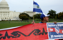 A Salvadoran man holds his nation's flag and a sign during a protest rally for immigrants rights on Capitol Hill in Washington, D.C., Oct. 8, 2013.