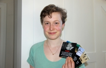 Environmentalist Emily Kelsall holds up samples of gas pump labels.
