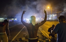 Demonstrators face off with police after tear gas was fired at protesters reacting to the shooting of Michael Brown in Ferguson, Missouri August 17, 2014.