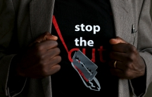 "A man shows the logo of a T-shirt that reads ""Stop the Cut"""