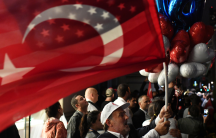 A supporter of Turkish President Tayyip Erdogan waves a US and Turkish flag as he waits for him to arrive outside of The Peninsula hotel in Manhattan, New York City, Sept. 19, 2017.