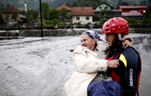 A member of the rescue team carries a women as they leave her flooded house in Topcic Polje, near Zepce May 16, 2014. The heaviest rains and floods in 120 years have hit Bosnia and Serbia.