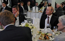 Russian President Vladimir Putin, right, sits next to retired US Army Lt. Gen. Michael Flynn