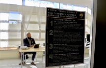 Window with poster about how to handle immigration raids, man behind at table