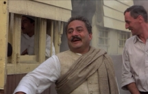 A screen shot from Gandhi with extra Aseem Chhabra as a passenger in the background on the train. In the foreground is Saeed Jaffrey (left) as Sardar Patel and Gunter Maria Halmer playing Herman Kallenbach.