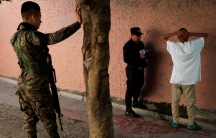 Police interrogate a suspected gang member against a wall with his hands behind his head.