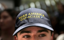 A man wears a Make America Gay Again hat.