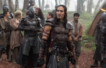 A man in an armor stands alongside other men in armor.