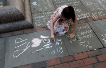 A girl writes a message in chalk on the pavement in central Manchester, Britain.