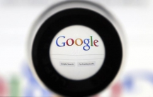A magnifying glass centers in on the Google logo.