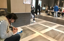 Man sits in polling place with binder